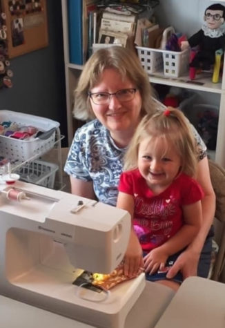 Jackie Larson with her granddaughter making a mask in their sewing machine. Larson has been making free masks for the community since the beginning of the pandemic.
