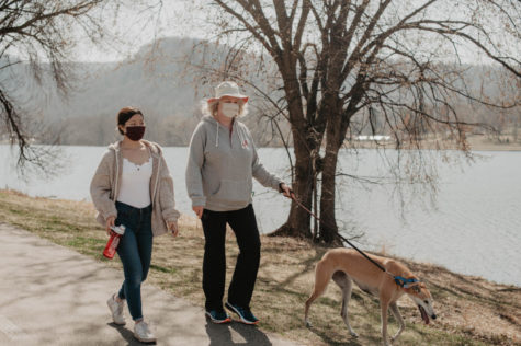 First-year student Macey Heath (left), her mother Caroline (right) and their dog walking on the path of Lake Winona Saturday morning. Heath said she maintains physical activity during COVID-19 by going to the rock climbing center and going on walks when weather permits.