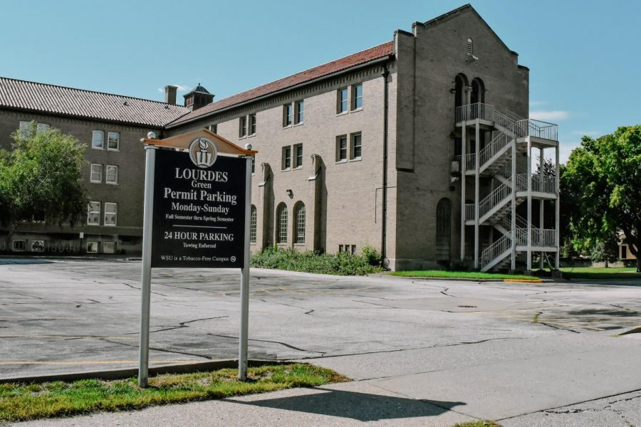 Lourdes Hall, now sitting empty of student life and activity, its parking lots empty as well.