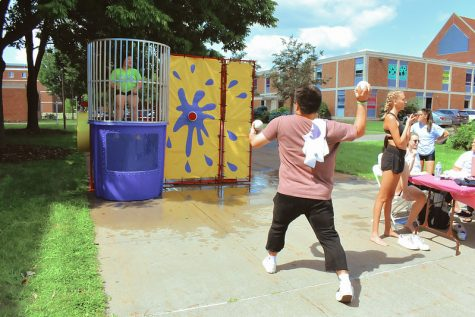 Student interacting with Greek Life's Dunk Tank.